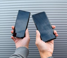 photo of two iphones being held up with grey background
